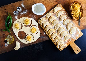 Pierogi on a serving board with some waiting to be assembled