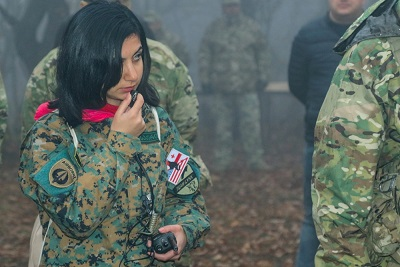 A woman in military uniform interprets into a small microphone.