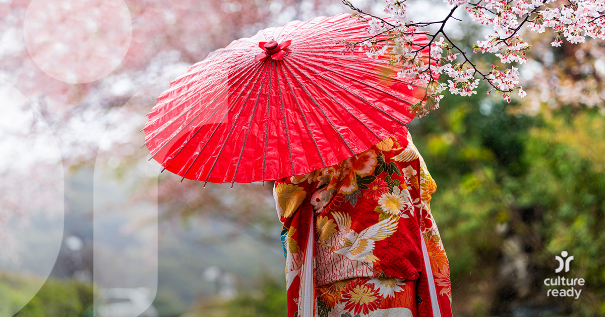 A woman in a red kimono holds a red umbrella in front of cherry blossom flowers