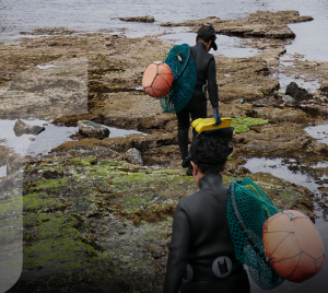 Women in diving suits walking on a beach, carrying fishing nets.