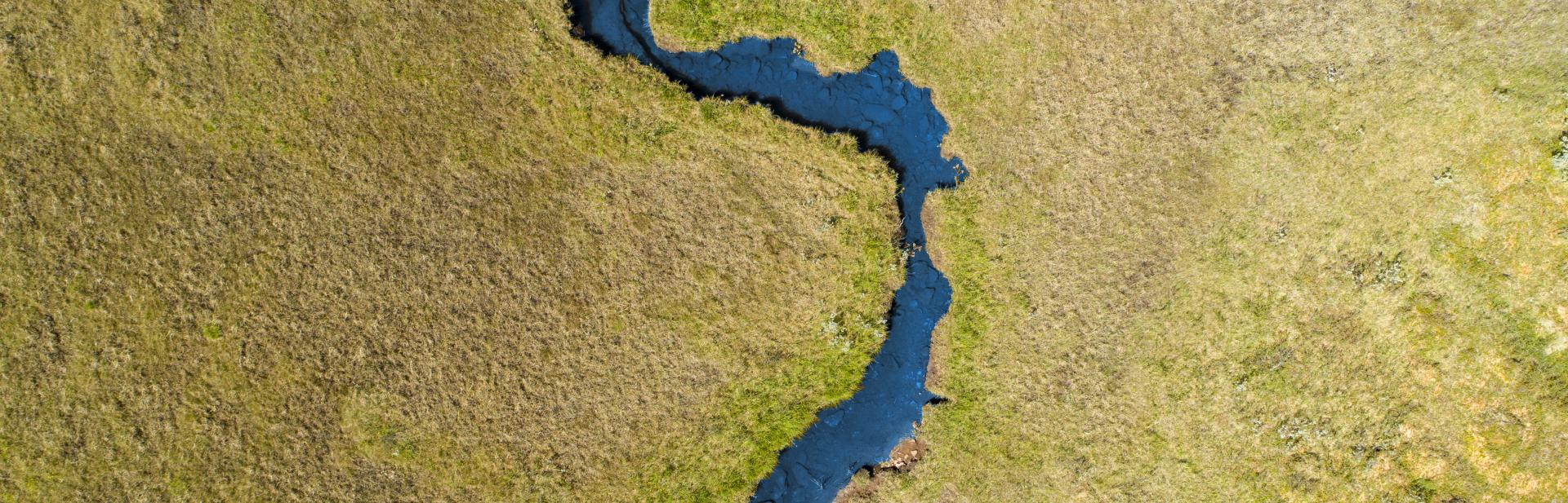 Aerial view of river winding through grasslands.