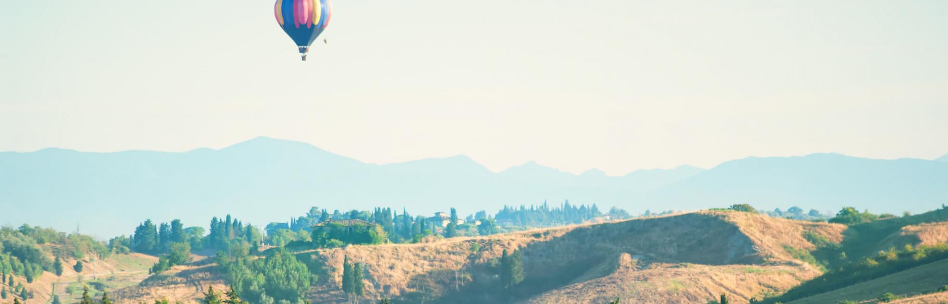 A graceful countryside with a hot air balloon floating over it.