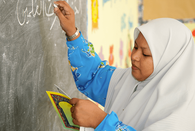 Female Instructor with Hijab writing on chalkboard in Malaysia.