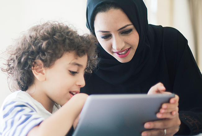 Middle eastern mother helping her child looking onto a tablet device.