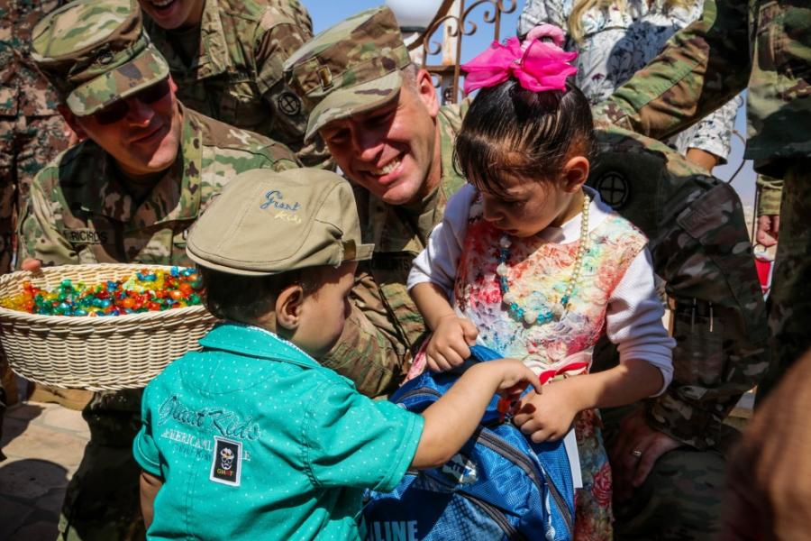 Two servicemen giving school supplies to Jordanian children