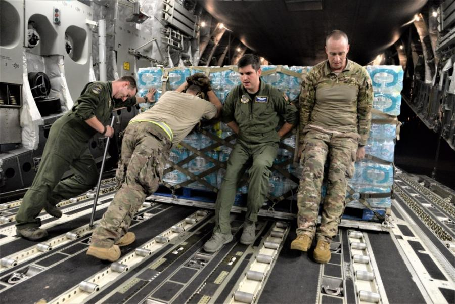 Airmen unload food and water from a C-17 Globemaster III to be distributed to hurricane survivors at San Juan Luis Muñoz Marín Airport in San Juan, Puerto Rico, on Sept. 30, 2017.