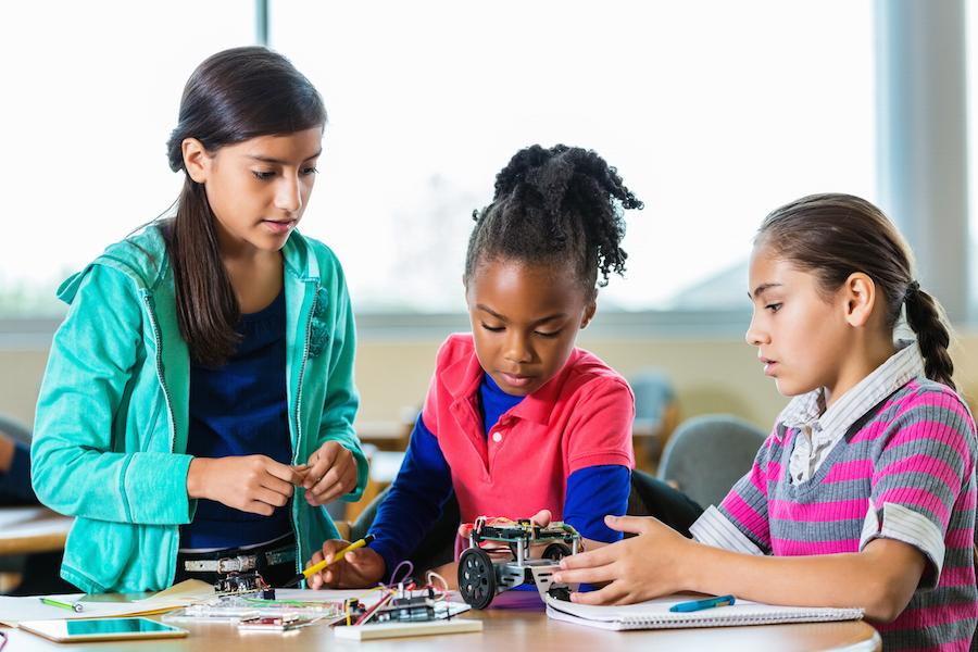 Three girls building a robot