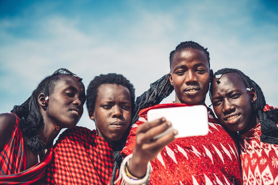 Four Maasai men looking at a cell phone