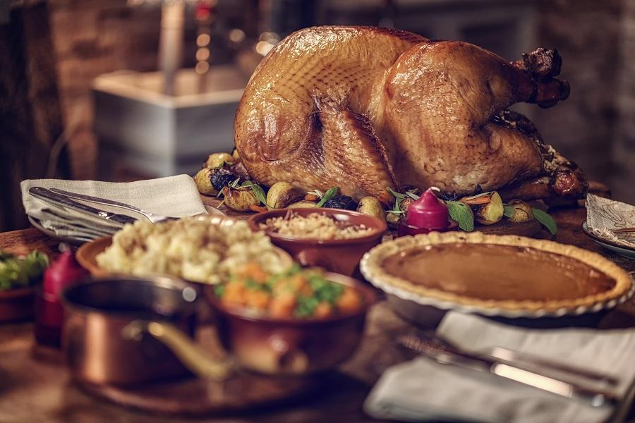 A cooked turkey sits on a table next to a pumpkin pie and other side dishes.