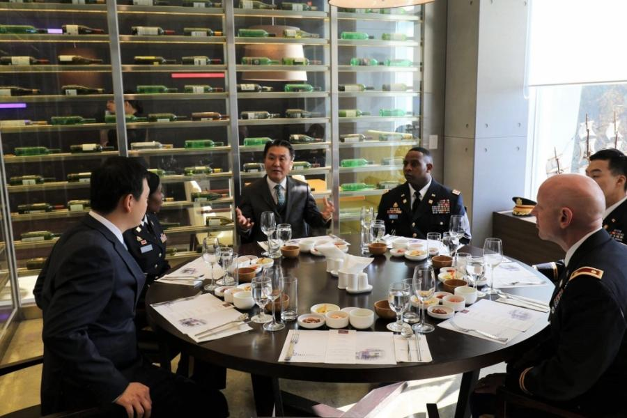Officers assigned to the 25th Transportation Battalion, Materiel Support Command Korea, 19th Expeditionary Sustainment Command, are seated at the 42nd Street Restaurant, where students majoring in hotel culinary arts at Daekyeung University cook and serve them lunch dishes as a part of the university's Good Neighbor Program, Daekyeung University, Gyeongsan, Korea.