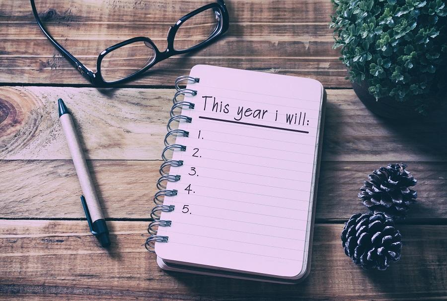 "Notebook on wooden table surrounded by a pen, pinecones, classes, and a plant. The notebook says ""This year I will"" and is followed by a numbered list."