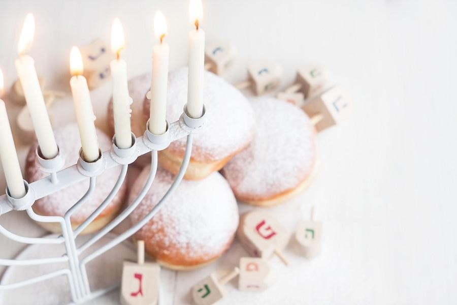 Image of a menorah above a plate of doughnuts.