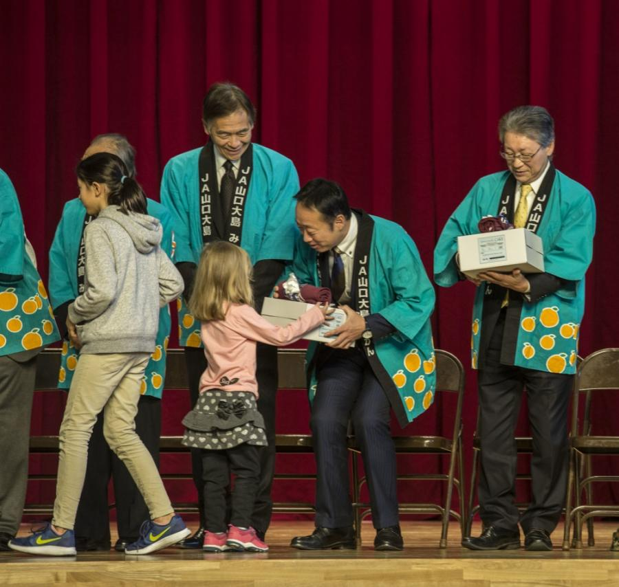 Students from Matthew C. Perry Elementary and Iwakuni Elementary present guests with thank-you gifts during a mikan presentation Marine Corps Air Station Iwakuni, Japan.