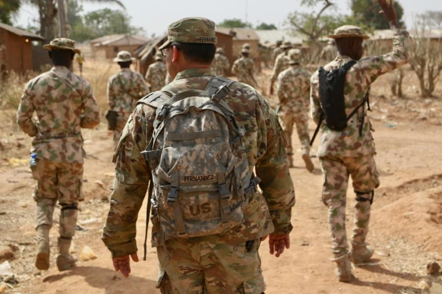 U.S. Army Soldiers walking with Nigerian Army Soldiers in a remote military compound four hours north of the capital in Jaji.