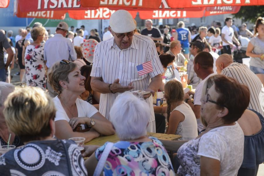 An older man holding an American flag stands talking to a group of people sitting at a table.
