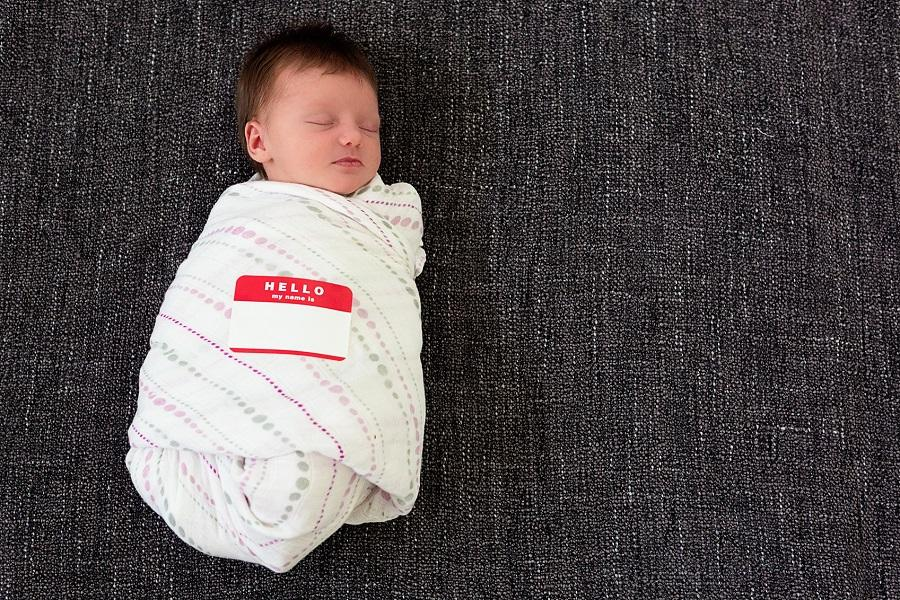 "A baby swaddled in a blanket with a name tag on the blanket that says ""Hello my name is."""