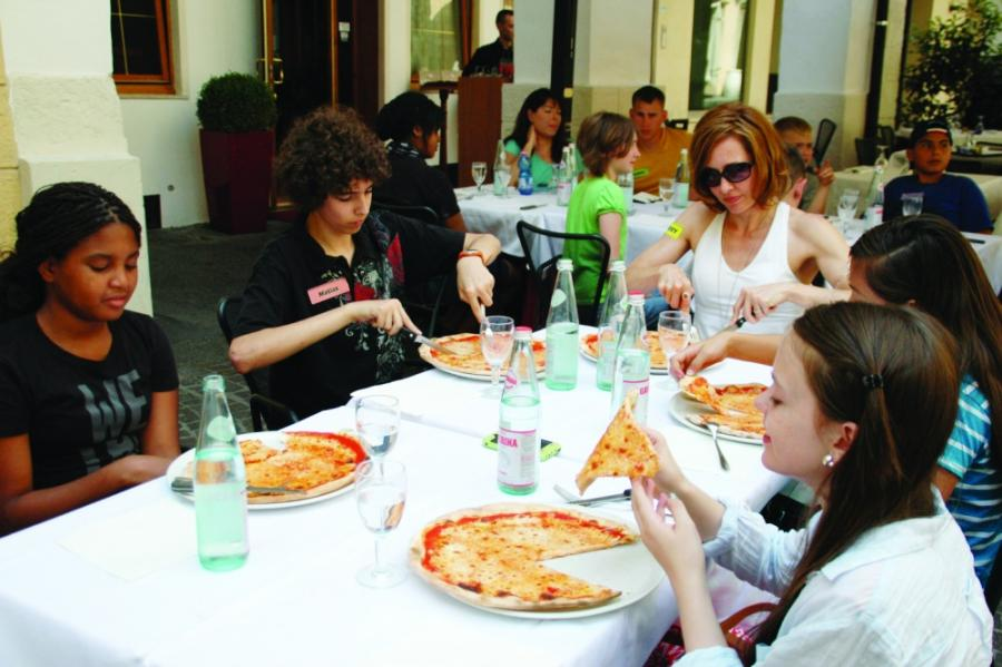 Students in the military community sit at a table eating pizza in Italy to learn cultural and regional facts.