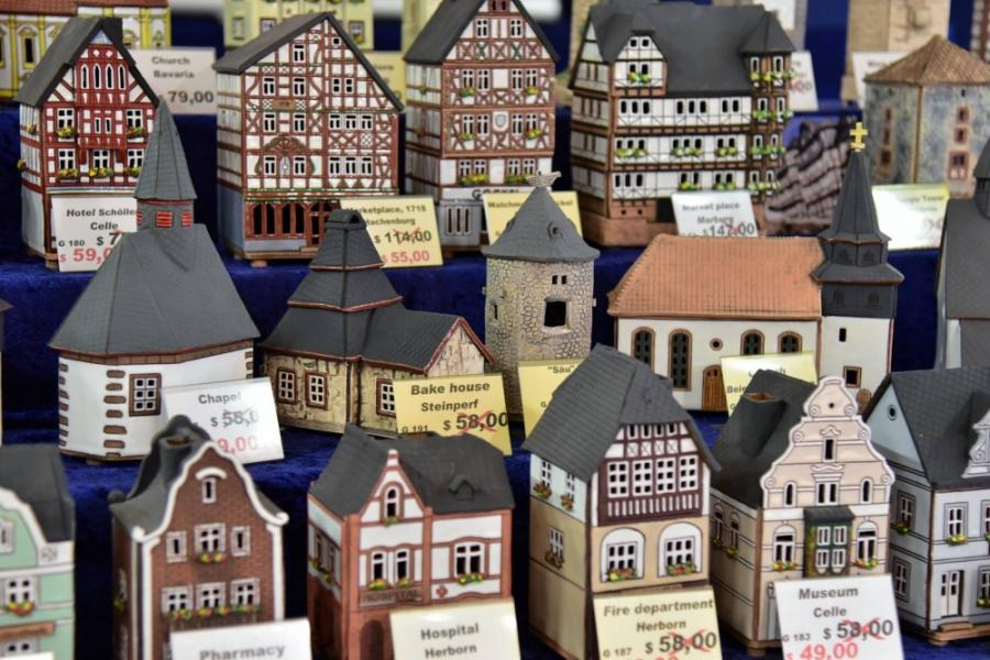 Image of artisan-crafted miniature buildings on sale with prices marked.