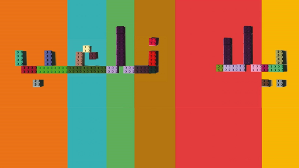 "Colorful image of the words ""let's play"" in the Arabic script, formed by LEGO building blogs"