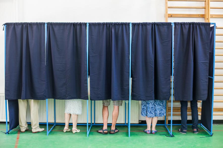 People standing behind curtains at a polling/voting station