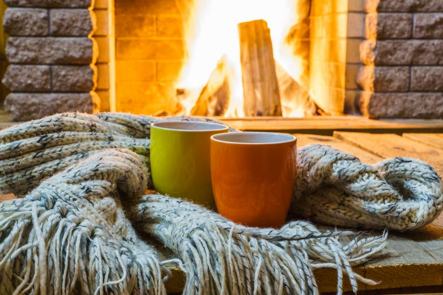 Two mugs surrounded by a blanket by a fire