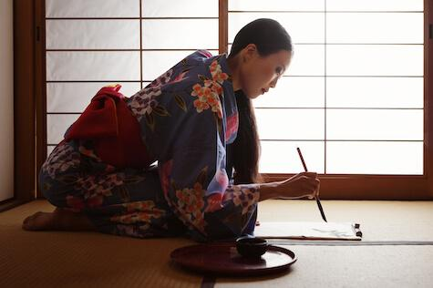 An Asian woman in a traditional house leaning over paper with a calligraphy brush.
