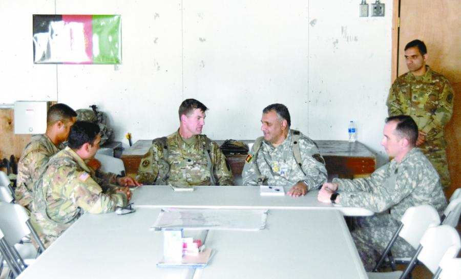A group of men in military uniforms seated around a table, talking, interpreter in background