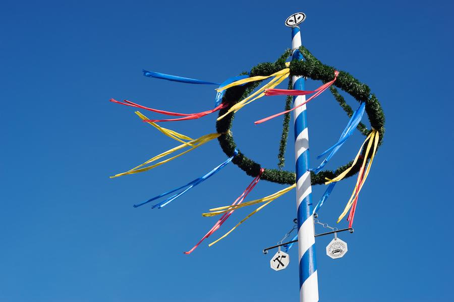 Top of a maypole in Germany, with colorful ribbons hanging off of a wreath