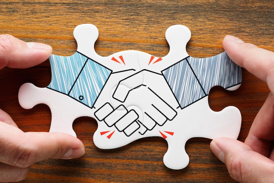 Two puzzle pieces linked together depicting a handshake