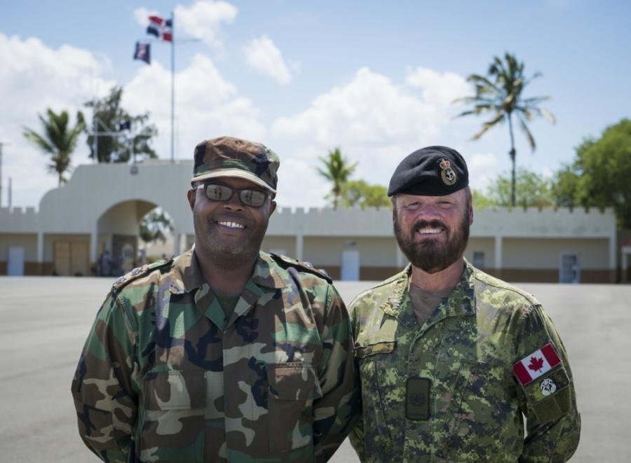 Two men in military uniforms pose for a photo outside