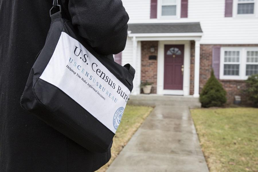 Close-up of a messenger bag with U.S. Census Bureau information on the outside. The person wearing the bag is approaching a house.