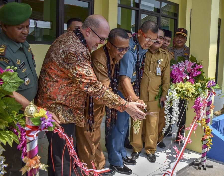 Members of the US Navy and Indonesian Marines cut the ribbon as part of a ceremony for the opening of a school