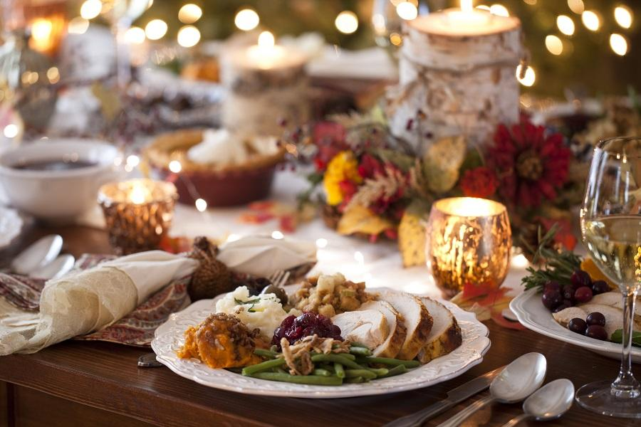 Close-up shot of a dish on a festively-decorated table. The plate has traditional Thanksgiving dishes on it: turkey, green beans, cranberry sauce, sweet potatoes, mashed potatoes, and stuffing.