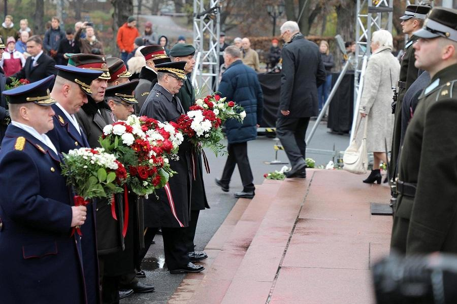 Military leaders of allied nations stand with flowers in hand, to take part in a Flower Laying ceremony at Riga's Freedom Monument