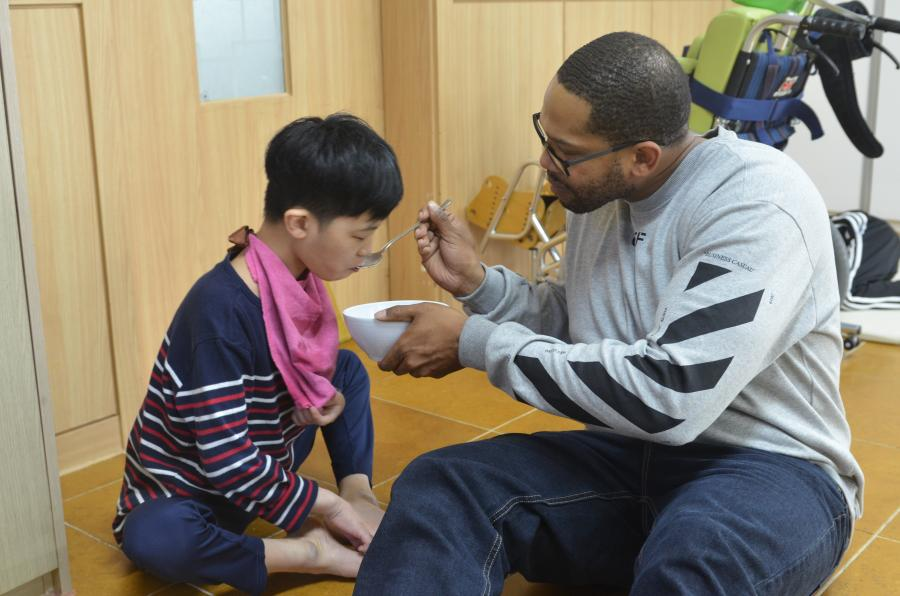A soldier feeds a special needs resident in an orphanage.