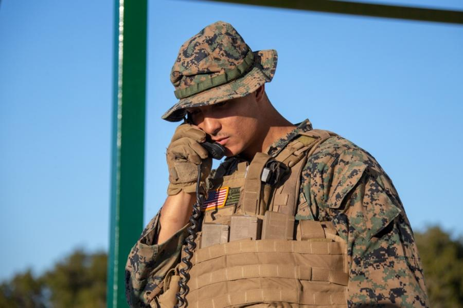 A Marine Corps radio operator is holding a phone to his hear.