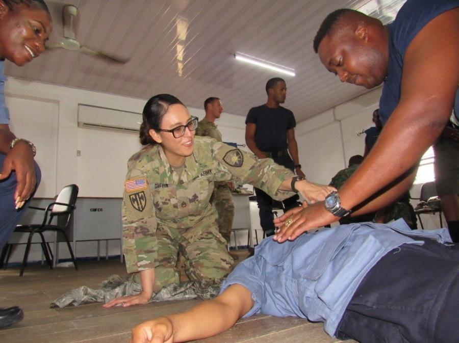 A Florida Army Guard medic with the 256th Medical Company Area Support (MCAS), shows the procedures to perform first aid for an open chest wound to members of Guyana's defense force and coast guard.