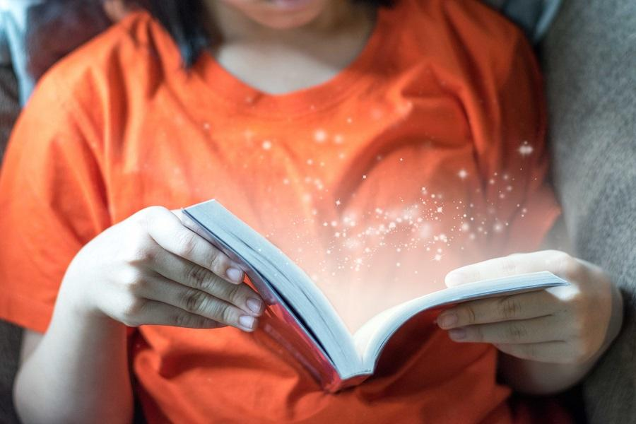 Close-up of a young girl reading a young adult fiction book with a magical sparkle light effect coming out of the book.