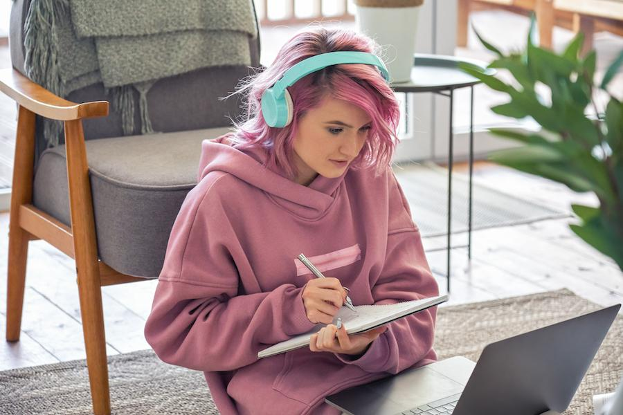 A woman with pink hair, wearing a pink hoodie and light blue headphones, is sitting on the floor with her back to a chair and a laptop on her lap. She is holding a notepad and is writing on it.