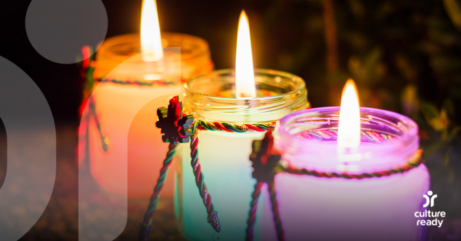 Image of three different colored candles, all lit.