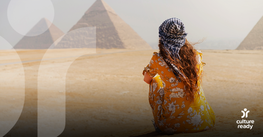 A woman wearing a bright orange dress and a blue checked headscarf facing away from the camera. She is looking at Egyptian pyramids in the distance.