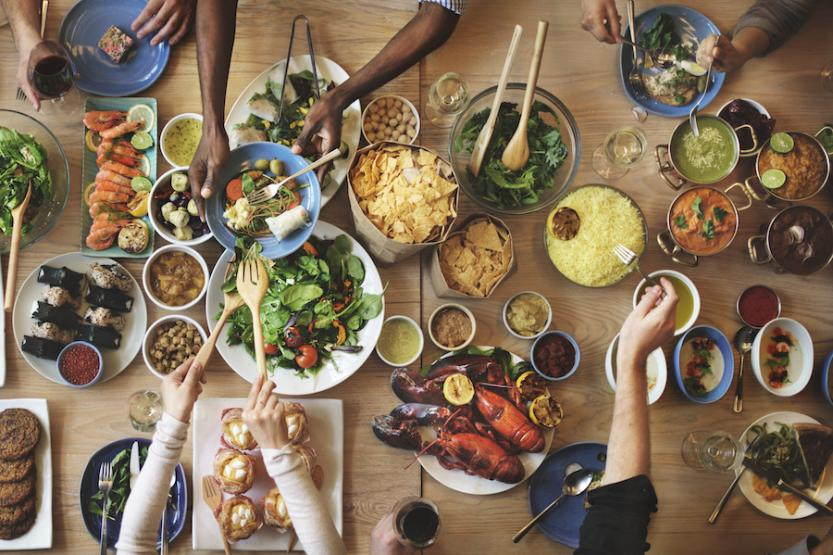 Table of many different dishes, with hands reaching in to take food