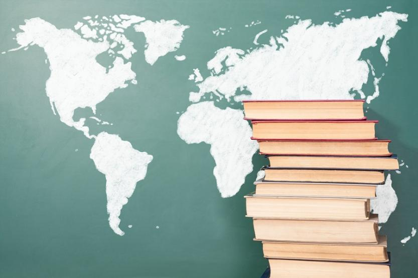 A stack of books in front of a map of the world