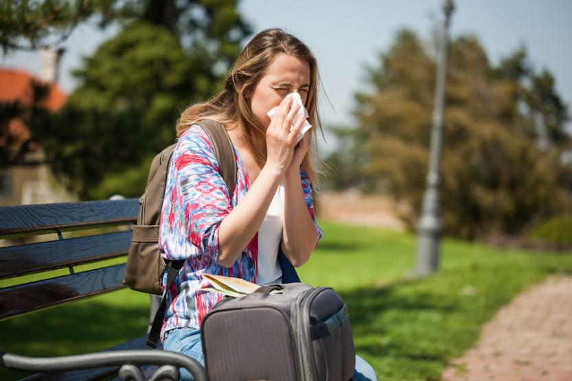 Woman wearing a backpack sitting on a bench, sneezing into a tissue next to a suitcase with a map on top.