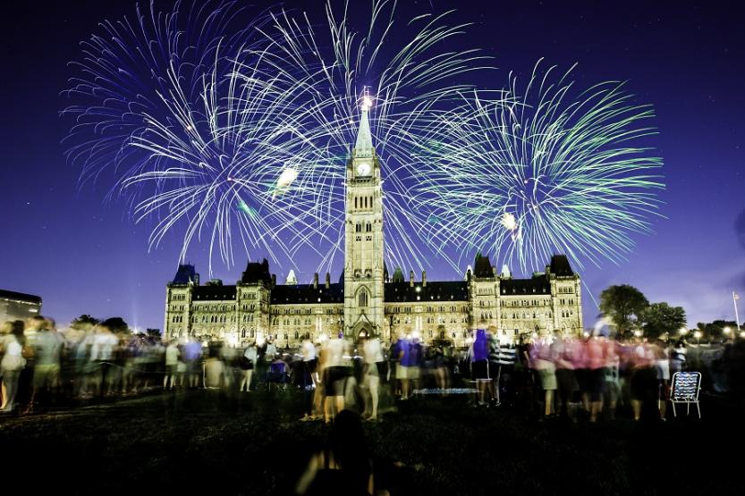 Nighttime Canada Day fireworks over Parliament on Parliament Hill in Ottawa, Ontario