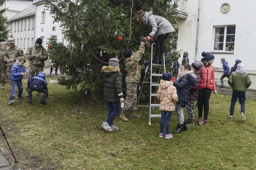 Children and soldiers gathered around a pine tree. A soldier is handing decorations to a woman on a ladder