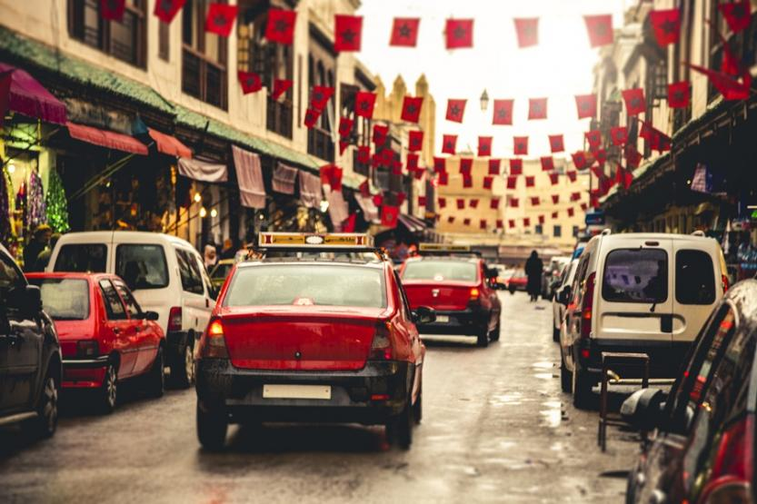 Red taxis in Fez, Morocco, driving down a street with cars parked on either side. Banners of the Moroccan flag hang between buildings.
