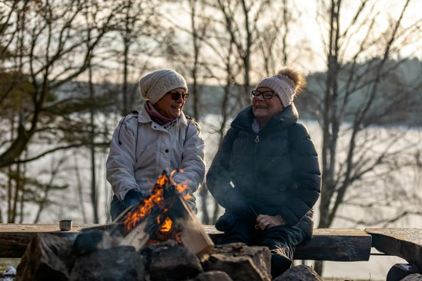 Two senior ladies are sitting on a bench by a burning campfire​ during wintertime.