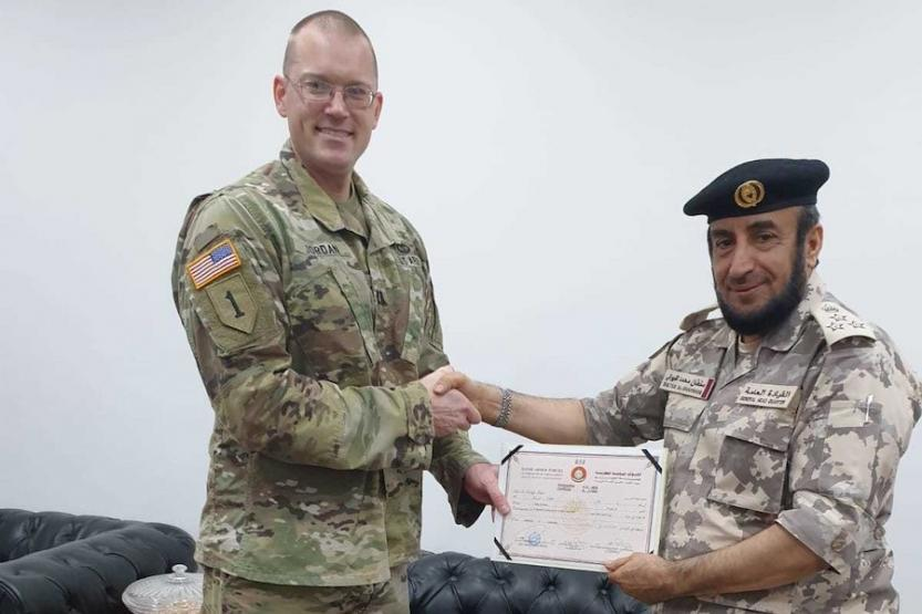 Capt. Allen Paul Jordan poses for a photo with Qatari Brig. Gen. Sultan Mohammed Sultan Al Shawani, a multilingual school commander. The two men are shaking hands.