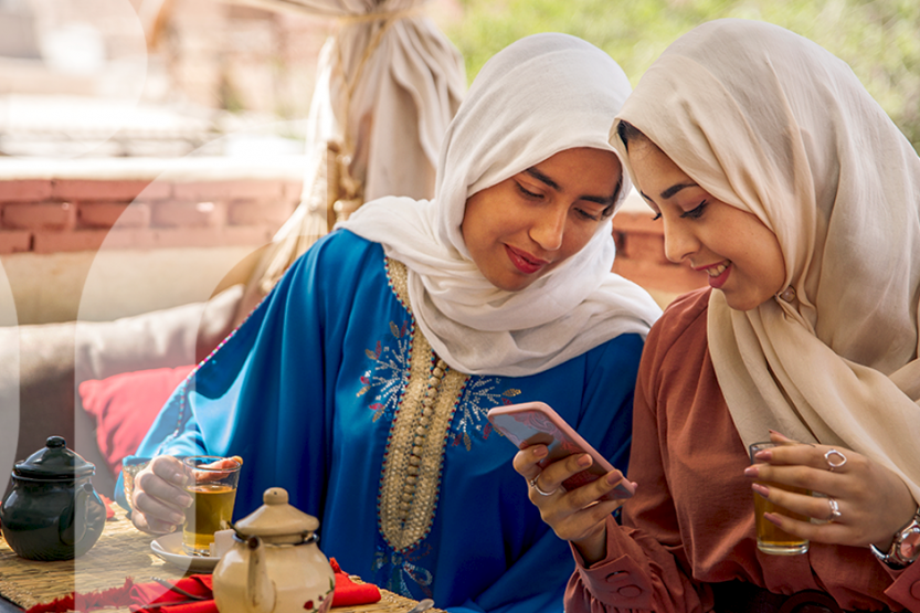 Two women in hijabs looking at a phone. One woman is holding a glass of tea.